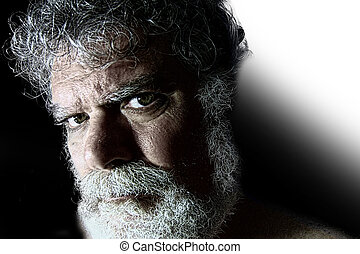 Mature bearded man with angry face staring