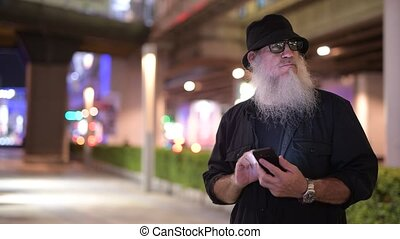 Mature bearded tourist man using phone in the city streets at night