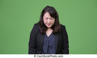 Mature beautiful Asian businesswoman giving thumbs down