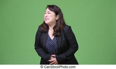 Mature beautiful Asian businesswoman having stomach ache