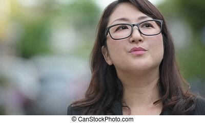 Mature beautiful Asian businesswoman thinking in the streets outdoors