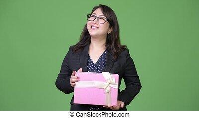 Mature beautiful Asian businesswoman thinking while holding gift box