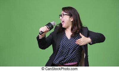 Mature beautiful Asian businesswoman using microphone
