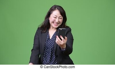 Mature beautiful Asian businesswoman using phone and getting good news
