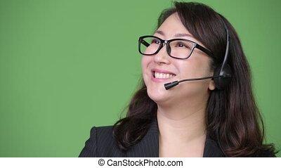 Mature beautiful Asian businesswoman working as call center representative