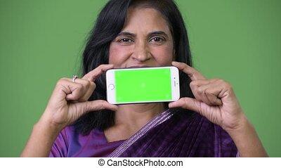 Mature beautiful Indian woman showing phone - Studio shot of...