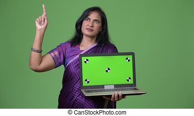 Mature beautiful Indian woman thinking while showing laptop...