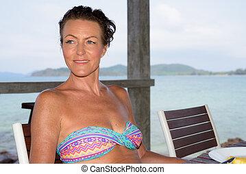 Mature beautiful tourist woman at the beach resort