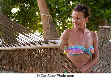 Mature beautiful tourist woman relaxing at the beach