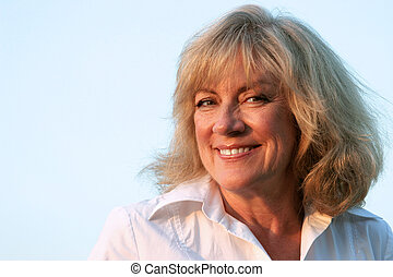 A beautiful, mature woman smiling in a warm, friendly manner.