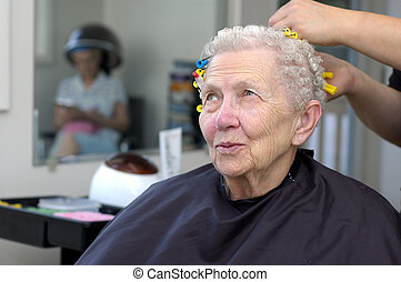 Happy senior woman getting her hair curled at a beauty salon.