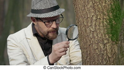 Mature biologist discovering forest environment with loupe...
