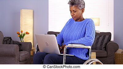 Mature Black woman sitting in wheelchair with laptop