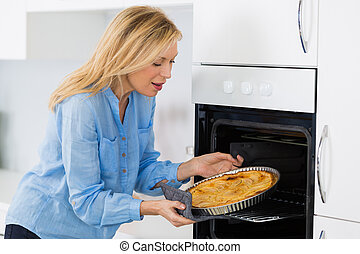 mature blond woman baking tart in oven