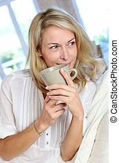 Mature blond woman in couch having a tea