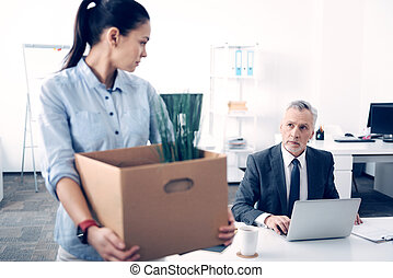 Mature boss looking at his employee leaving office