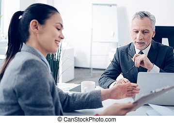 Mature boss talking with cheerful office worker
