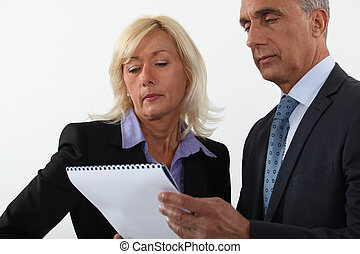 Mature business couple looking at a document