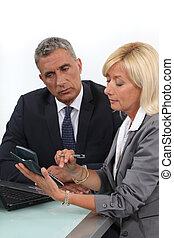 Mature business couple with a calculator
