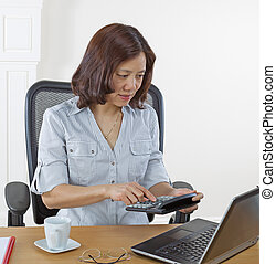 Mature business woman checking numbers with calculator