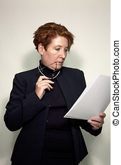 Mature business woman holding papers and reading glasses