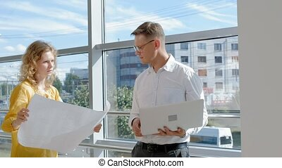 Mature businessman and businesswoman at a window with a laptop