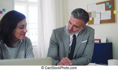 Mature businessman and businesswoman working together in office, talking.