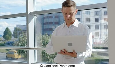 Mature businessman at a window with a laptop