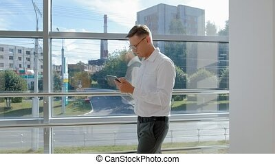Mature businessman at a window with a tablet