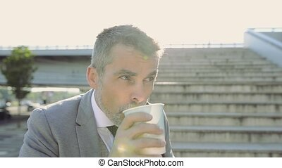 Mature businessman at the stairs in the city, drinking...