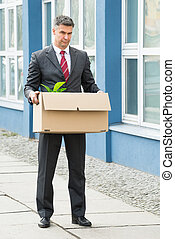 Mature Businessman Carrying Box