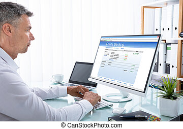 Businessman Doing Online Banking On Computer