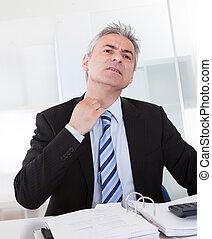 Portrait Of Mature Businessman Adjusting Collar At Desk