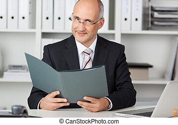 Portrait of confident mature businessman holding file at office desk