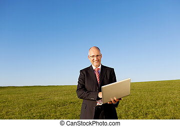 Mature Businessman Holding Laptop On Field