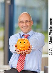 Mature Businessman Holding Piggy Bank In Office