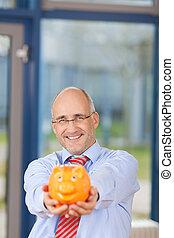 Mature Businessman Holding Piggybank In Office