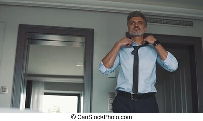 Mature businessman in a hotel room. - Mature businessman...