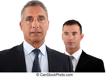 Mature businessman in front of a young colleague