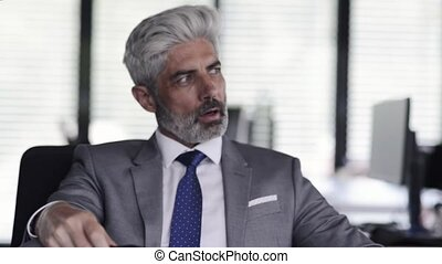 Mature businessman in gray suit in the office. - Mature...