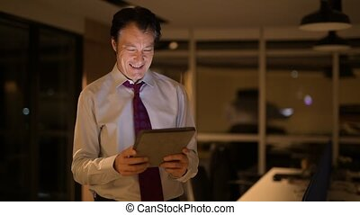 Mature Businessman In Office At Night Using Digital Tablet Computer