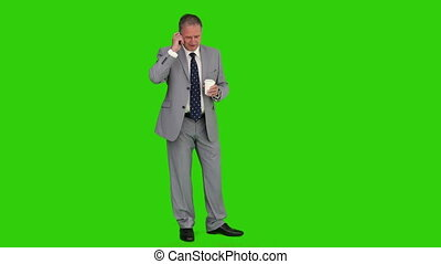 Mature businessman in suit having a phone call