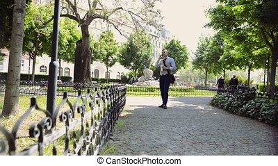 Mature businessman in the city park with coffee, making phone call.