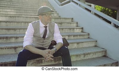Mature businessman in the city sitting on concrete stairs,...