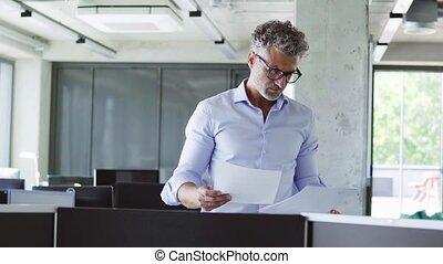 Mature businessman in the office holding documents.