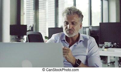 Mature businessman in the office drinking coffee. - Mature...