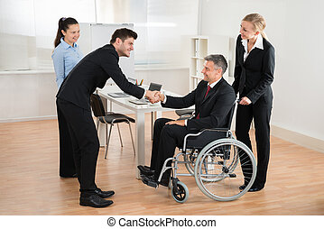 Businessman In Wheelchair Shaking Hands With Colleague
