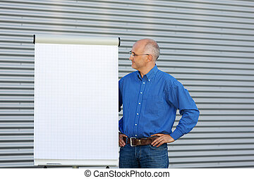 Mature Businessman Looking At Flipchart