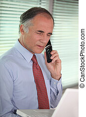 mature businessman looking at his laptop and talking on his cell