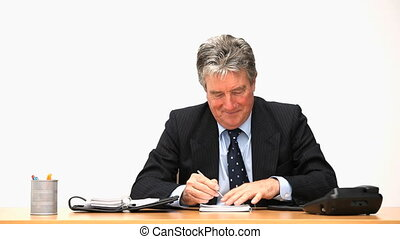 Mature businessman making a phone call at his desk